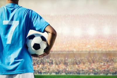 Football player in blue team concept holding soccer ball in the stadium