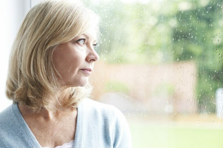 Mature lady looking out of the window, pensioner suffering from long Covid